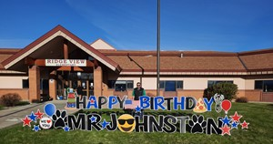 Ridgeview principal with a happy birthday sign on the grass